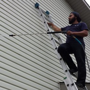 student pressure washing siding